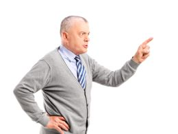 Full length portrait of an angry mature man pointing with finger